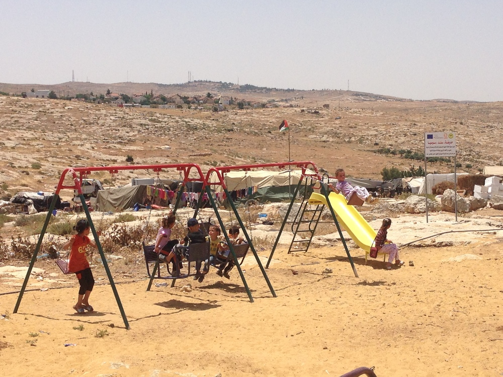 Children play at a playground in Susya - the Israeli settlement by the same name can be seen in the background.