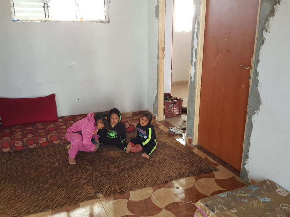 Three of Abeer's children in their cement house.