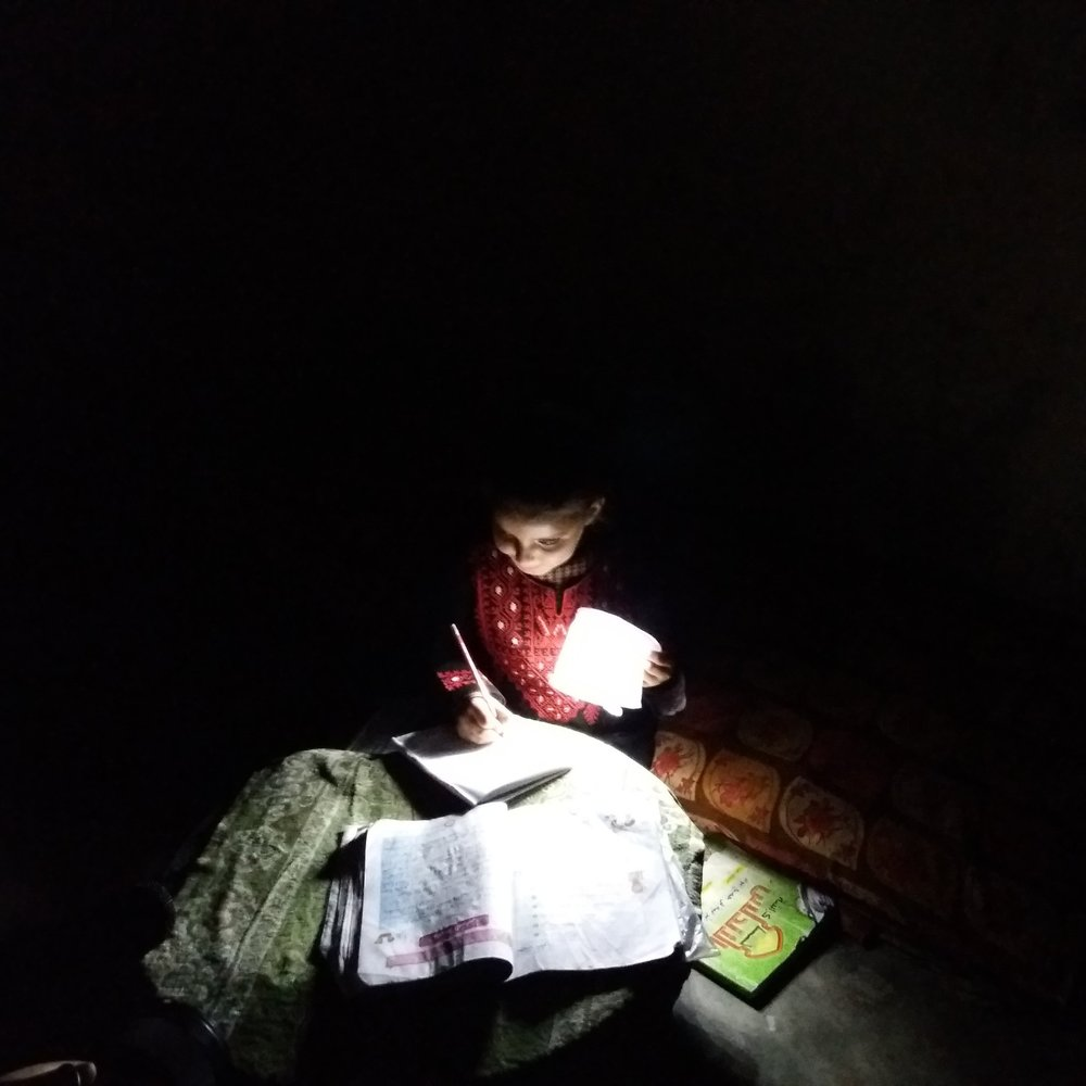 Maram reading with help from one of the solar lights donated by Rebuilding Alliance