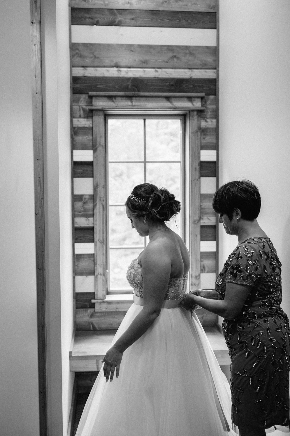 Mother of the bride tying bride's wedding dress bow in cabin at Grand View Lodge. Photography by Britt DeZeeuw.