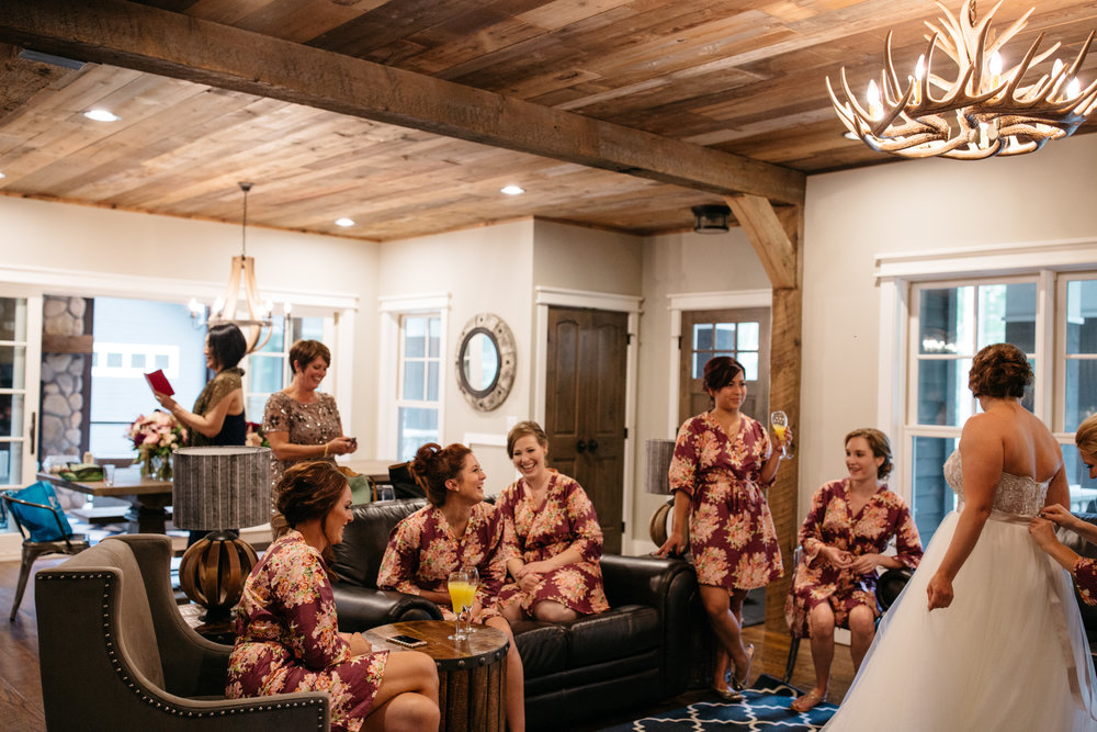 Floral print bridesmaids robes and mimosas in rustic chic cabin at Grand View Lodge in Nisswa Minnesota. Wedding Photography by Britt DeZeeuw