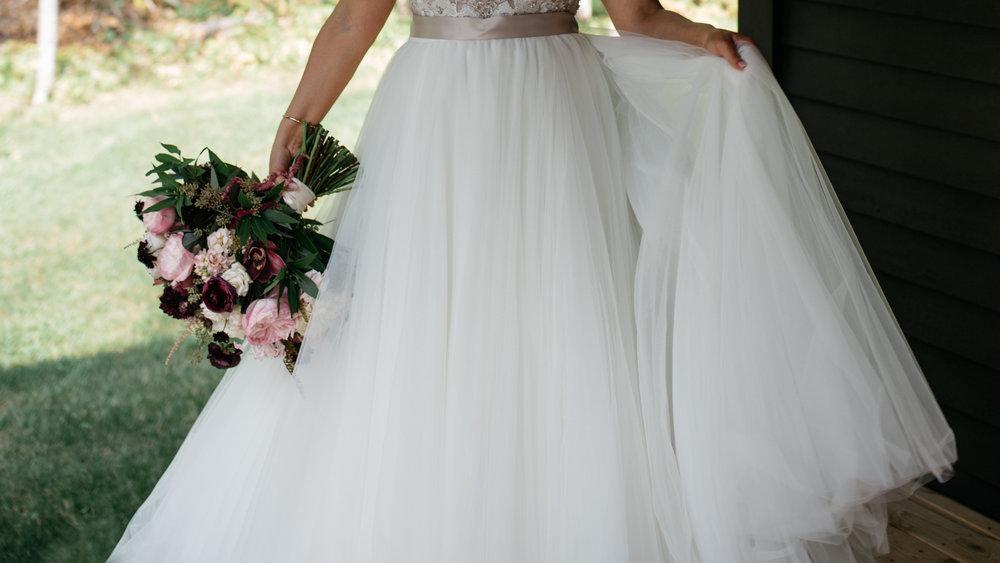 Bride with her beautiful wedding bouquet from Bloom Designs. Wedding Photography by Britt DeZeeuw, Brainerd Minnesota photographer