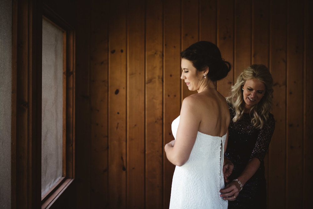 Mother of the bride buttoning up bride's lace wedding dress in cabin at Grand View Lodge. Photography by Britt DeZeeuw, Brainerd Minnesota fine art wedding photographer.