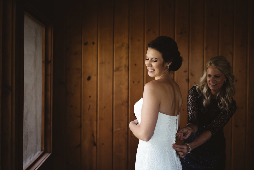 Mother of the bride zipping up bride's lace wedding dress. Photography by Britt DeZeeuw, Grand View Lodge wedding photographer.
