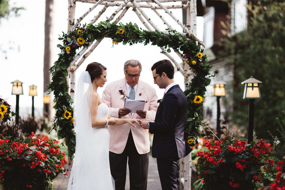 Exchanging rings during wedding ceremony at Grand View Lodge. Photography by Britt DeZeeuw, Brainerd MN photographer.