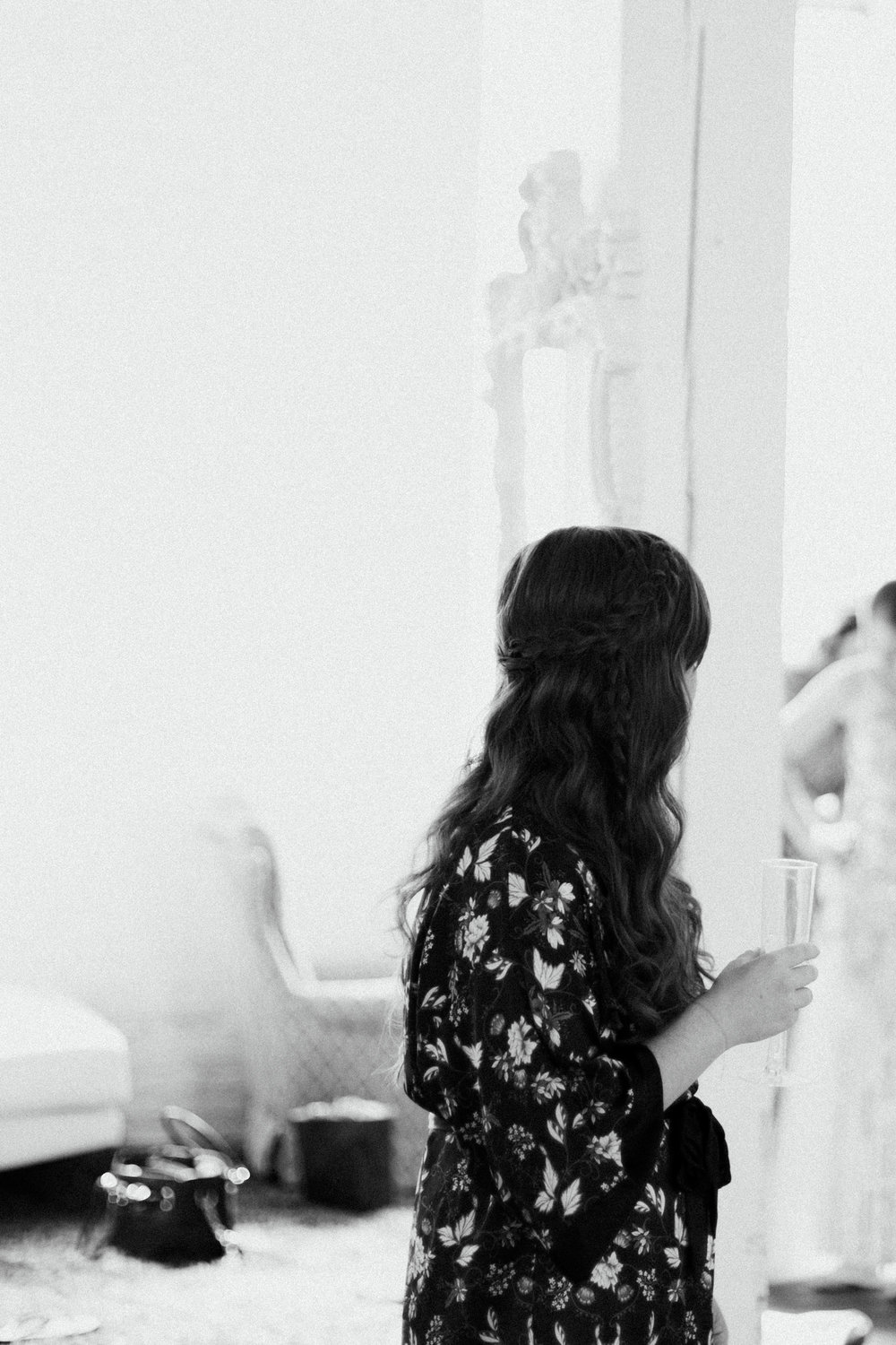 Bride in floral robe drinking a mimosa in the bridal suite. Photography by Britt DeZeeuw, NP Event Space wedding photographer.