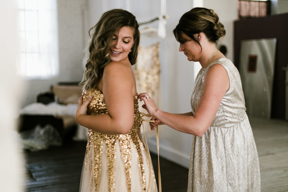 Bridesmaids getting into gold sequin dress in the bridal suite. Photography by Britt DeZeeuw, NP Event Space wedding photographer.