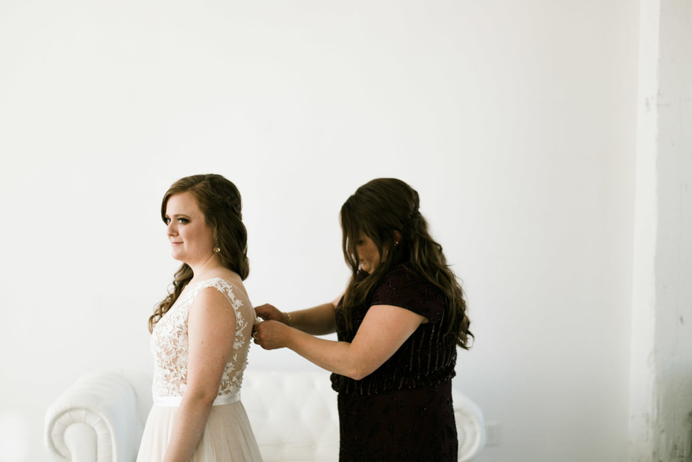 Bride getting into wedding gown in the bridal suite of the NP Event Space, photography by Britt DeZeeuw