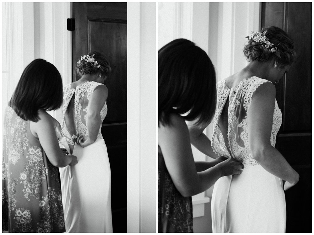 Sister helping bride get into dress at cabin wedding in Brainerd Minnesota