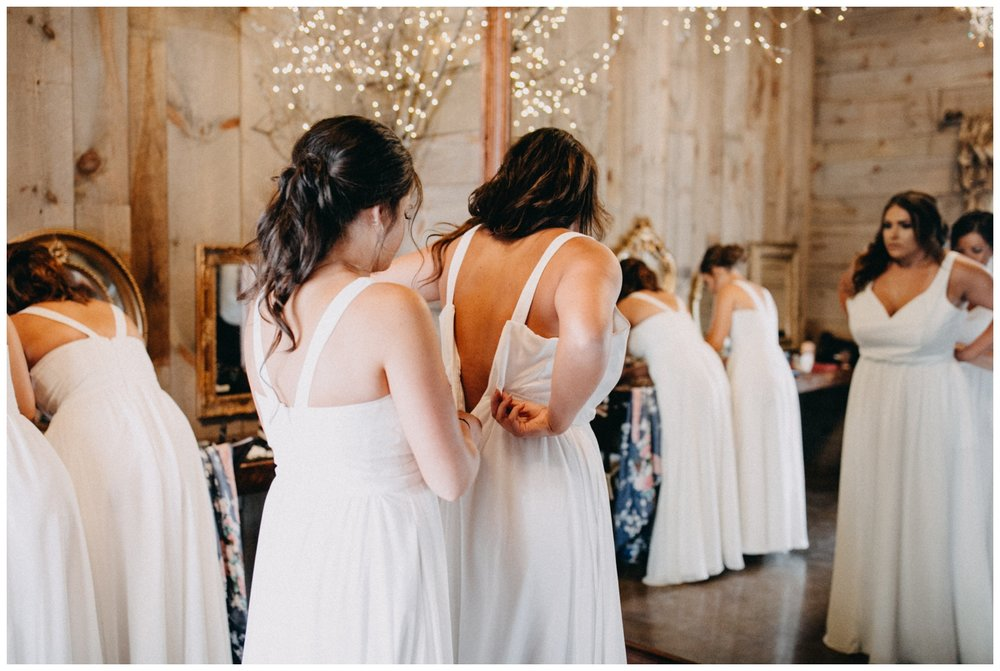 Bridesmaids helping each other get into white dresses at Creekside Farm Wedding