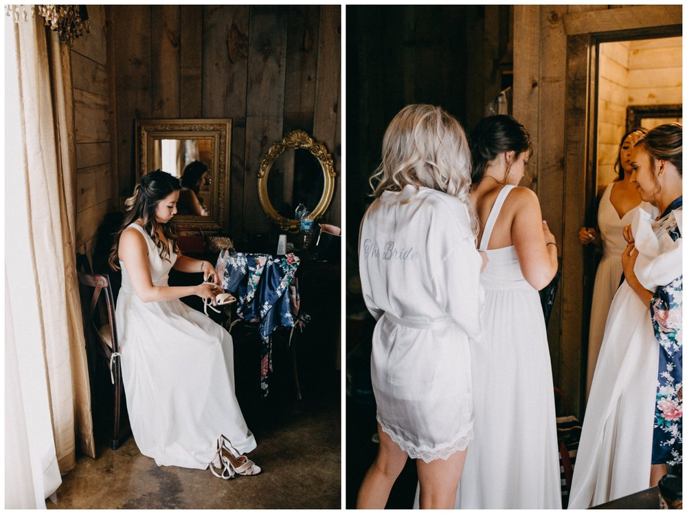 Bridesmaids getting into all white dresses at Minnesota barn wedding