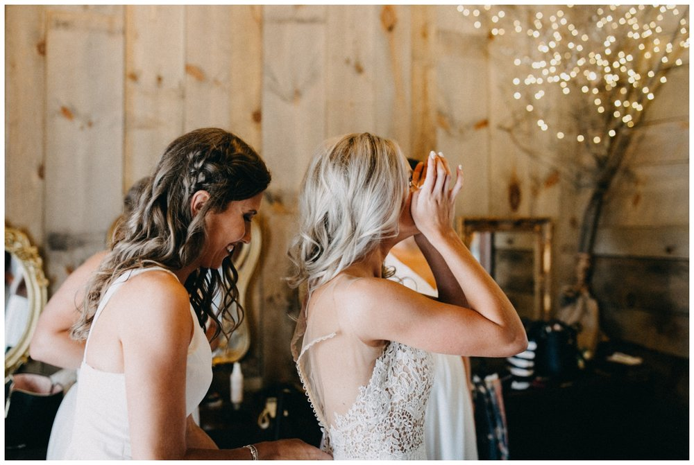 Emotional bride getting into wedding dress at Creekside Farm in Rush City, Minnesota