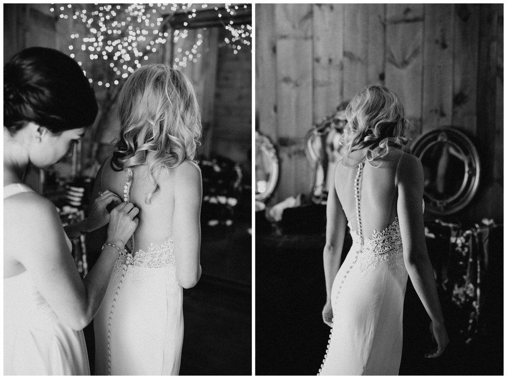 Bridesmaid helping bride put on wedding dress at Creekside Farm wedding