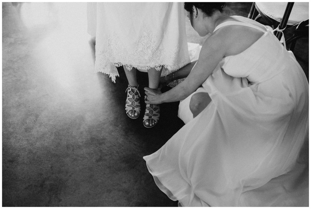Bridesmaid helping bride put on wedding shoes at Creekside Farm wedding in Rush City, Minnesota