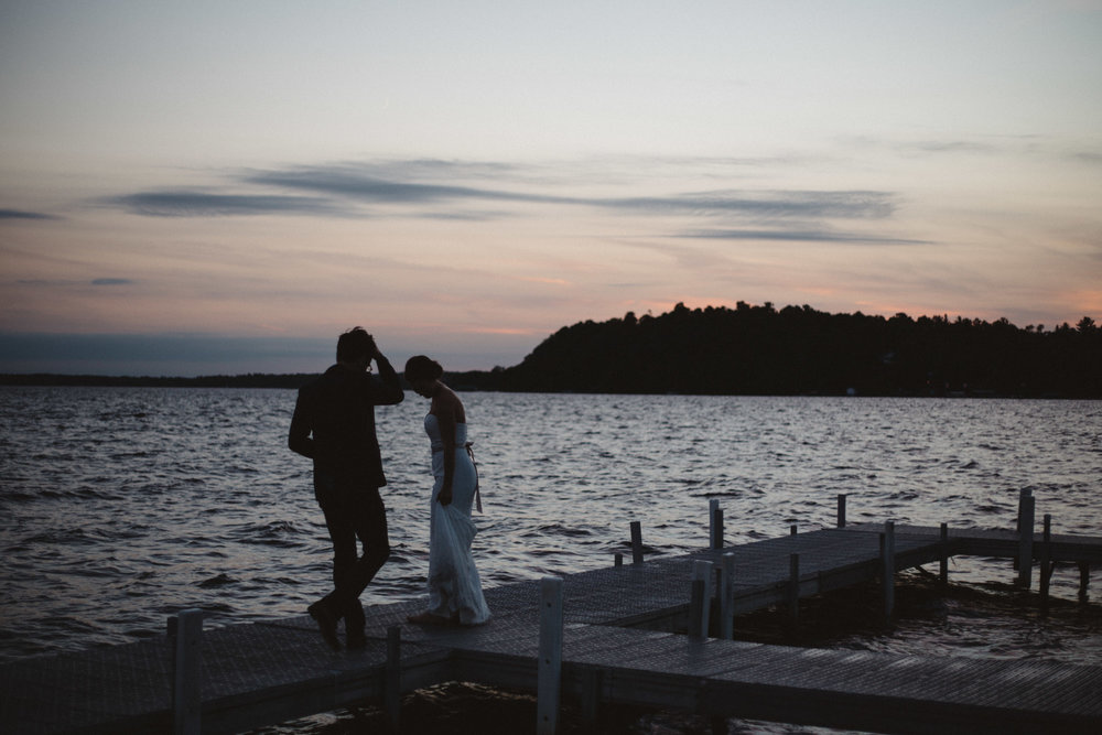 Bride and groom standing on dock during sunset at Gull Lake wedding