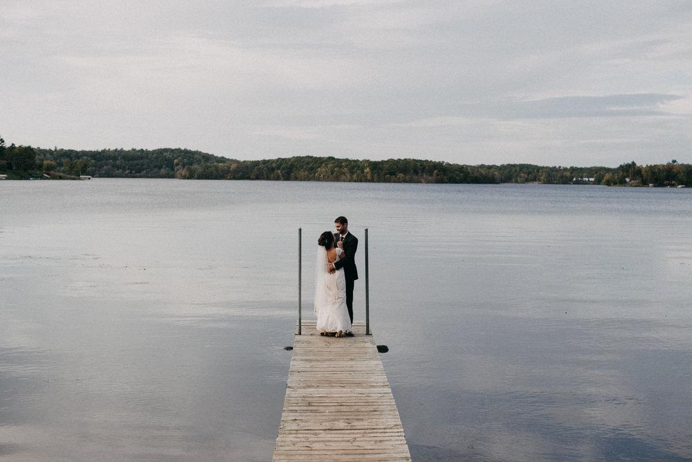 Bride and groom standing on dock at lake side wedding in Brainerd Minnesota