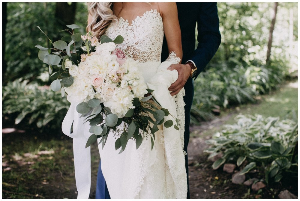 Bride with simple white floral and eucalyptus at Minnesota barn wedding