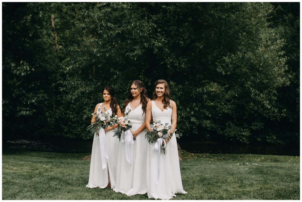 Bridesmaids in white dresses at Creekside Farm wedding ceremony