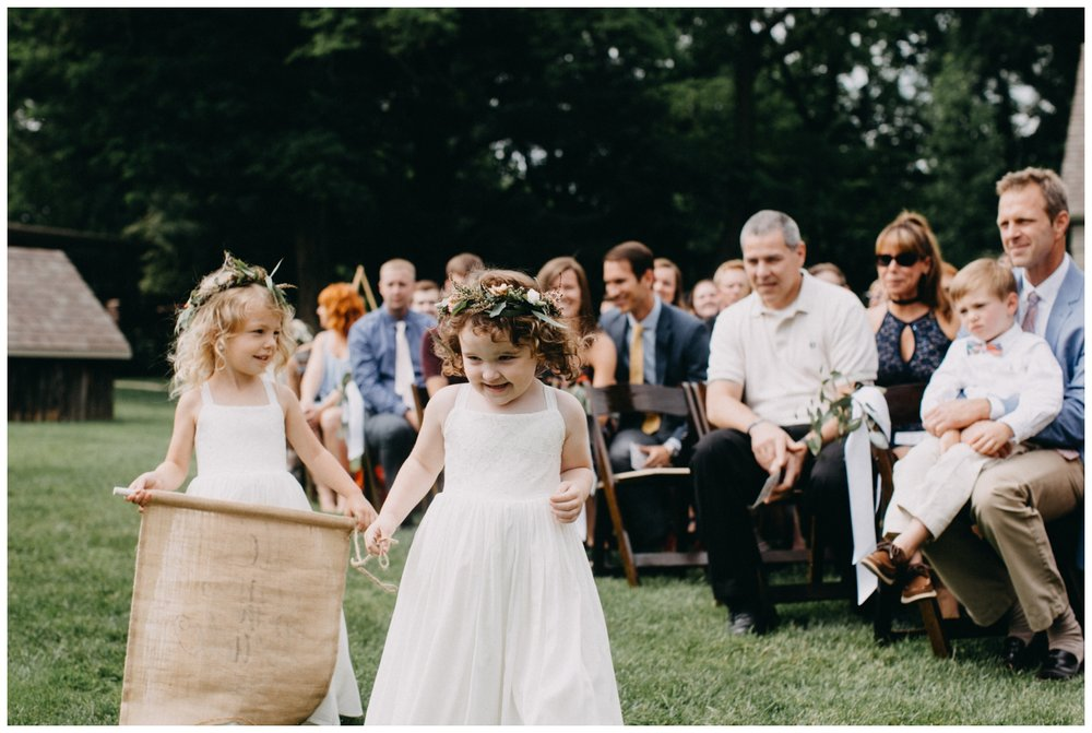 Adorable flower girls walking down aisle at Creekside Farm wedding