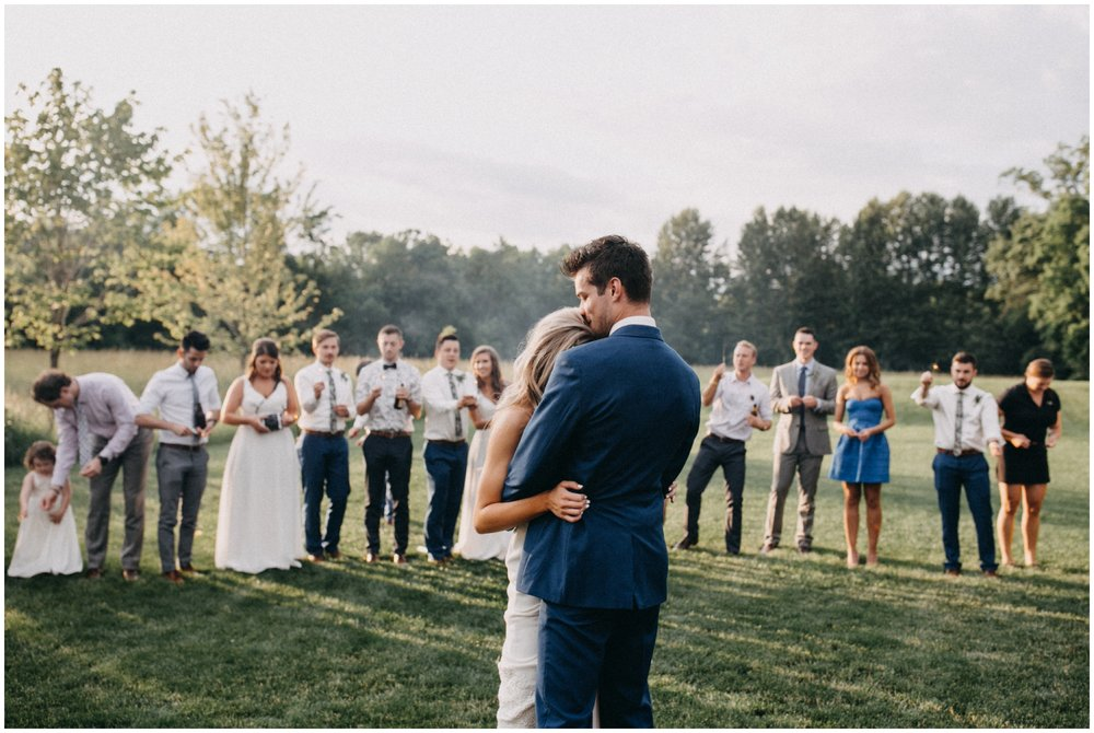 Bride and groom dancing at sunset while wedding guests hold sparklers at Creekside Farm