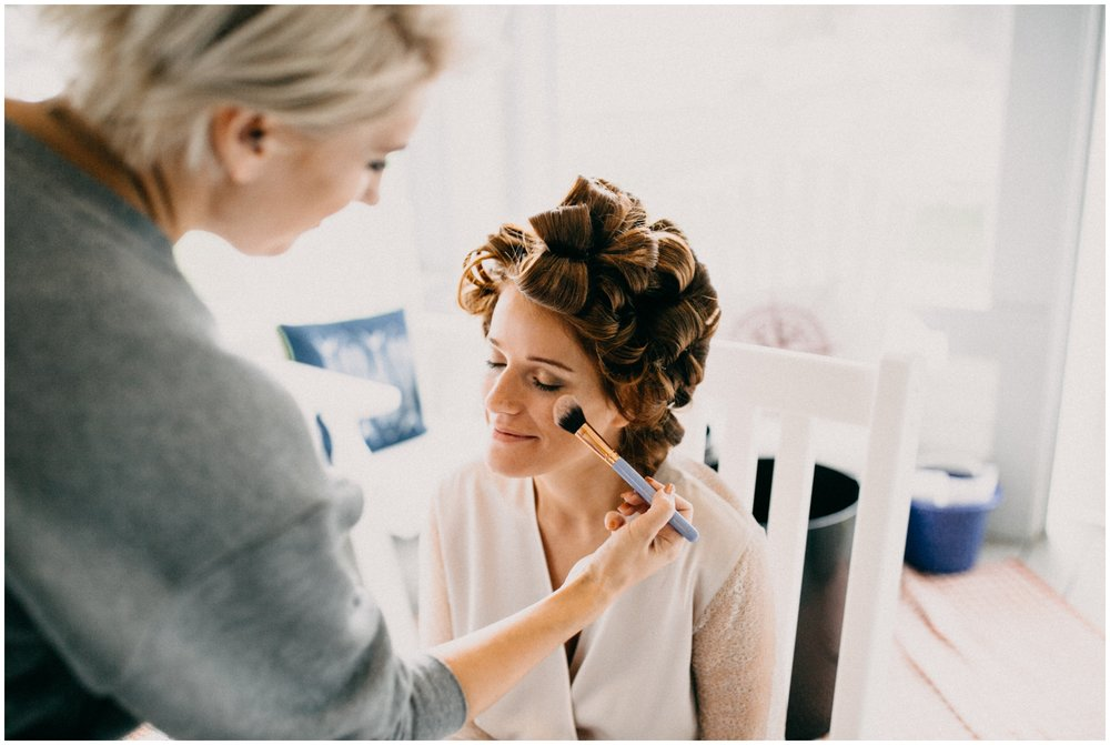 Bride getting make-up done at cabin wedding on Gull Lake, MN