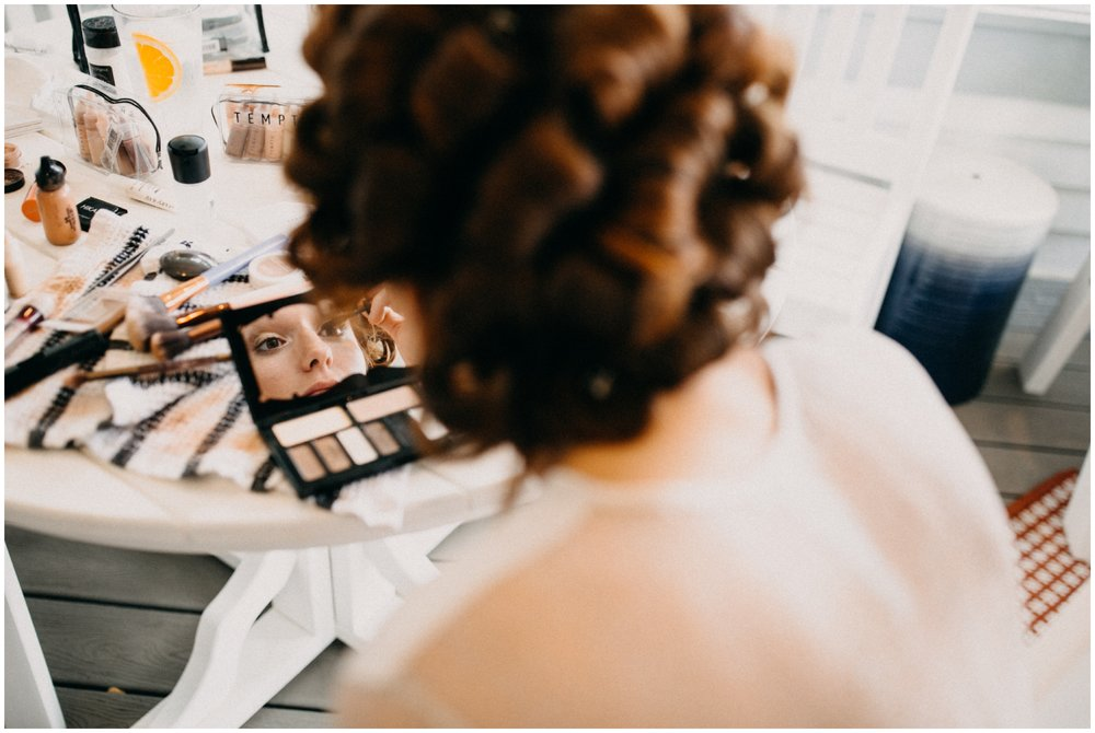 Red head bride in curlers getting ready at cabin wedding on Gull Lake