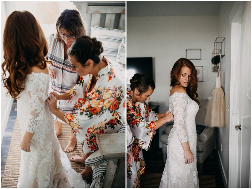 Sister helping bride get into wedding dress at cabin wedding on Gull Lake