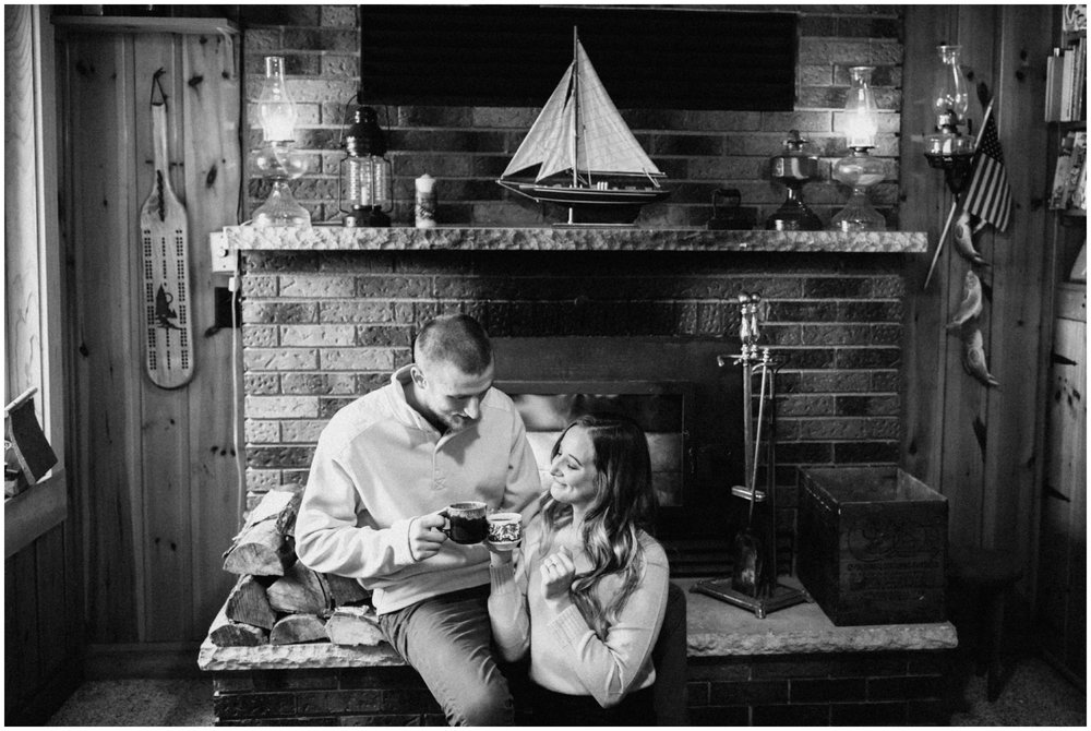 Engaged couple having morning coffee by the fireplace at MN northwoods cozy red cabin.
