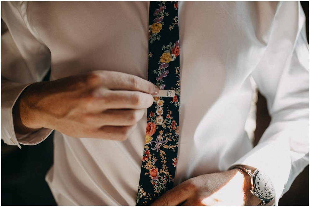 Groom wearing floral print tie with Minnesota tie clip at Camp Foley wedding in Pine River