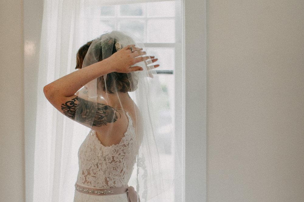 Bride putting on veil by Britt DeZeeuw, Duluth Minnesota wedding photographer