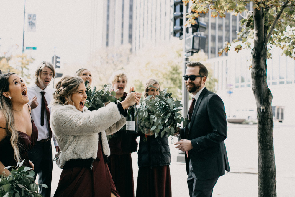 Bridal party popping champagne at St Paul wedding