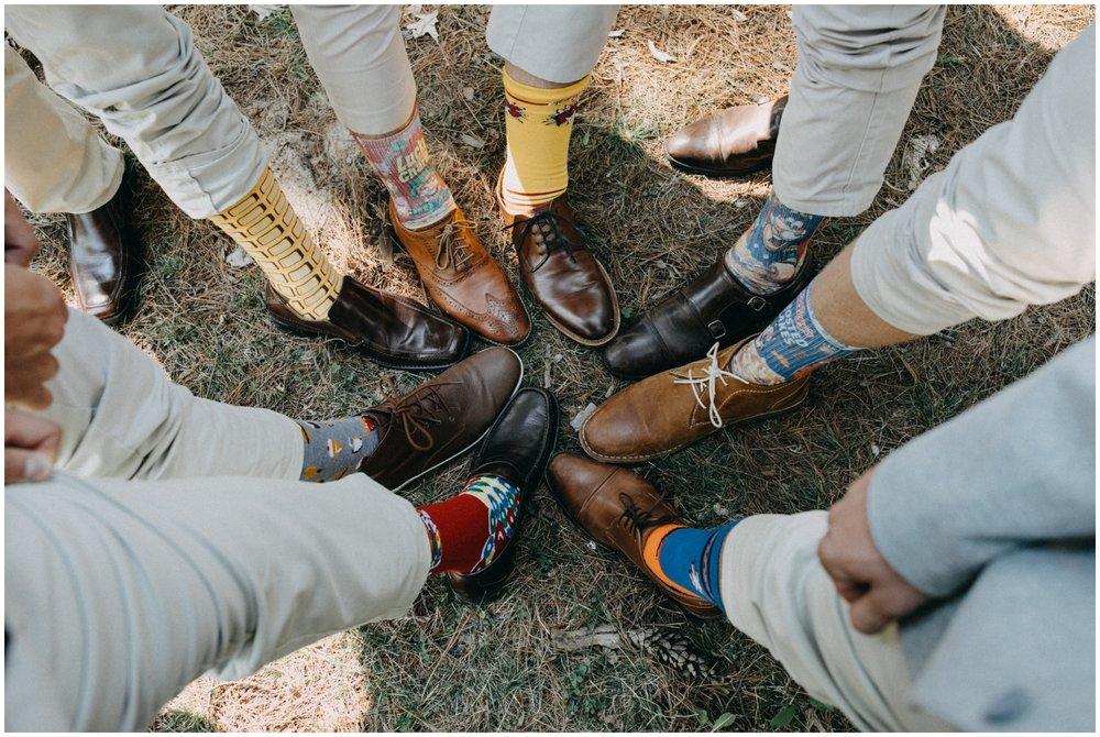 Groomsmen wearing cereal print dress socks at Camp Foley wedding