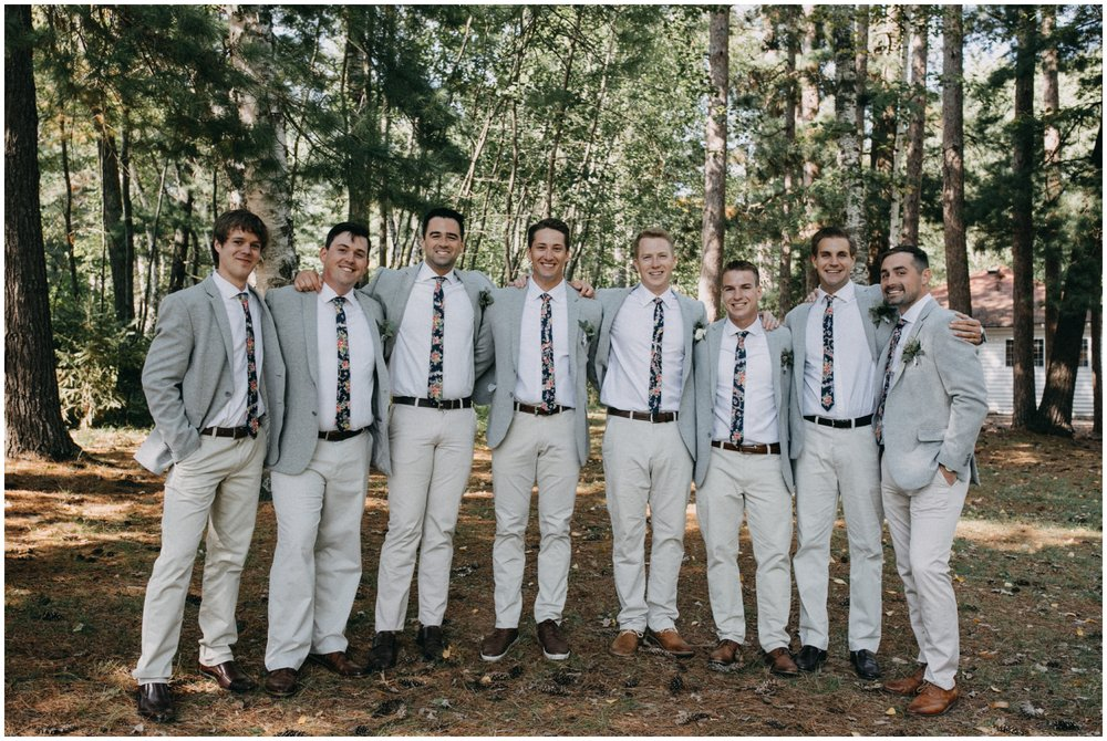 Groomsmen in casual grey coats and floral print ties at Camp Foley wedding