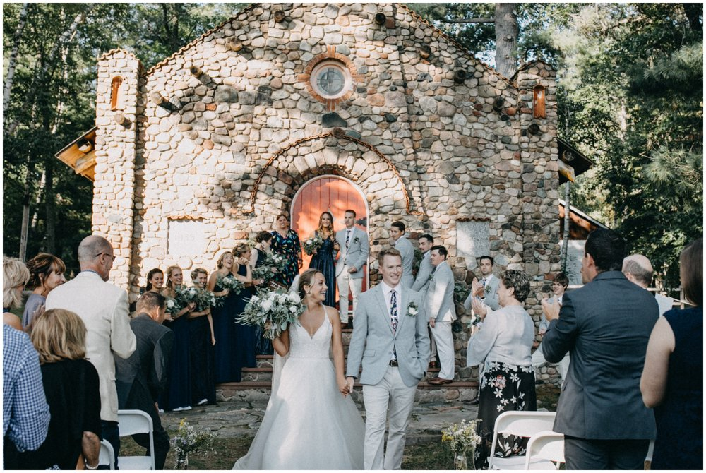 Romantic stone chapel wedding ceremony in the woods at Camp Foley Minnesota