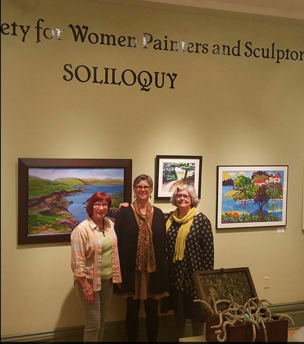 President Jackie Rybinski (center) with DSWPS members Linda Allen and Lori Zurvalec; paintings by Barbara Clay, Ruth Harvey, and Barbara Carr; sculpture by Janet Kondziela; photo by Dave Hands.
