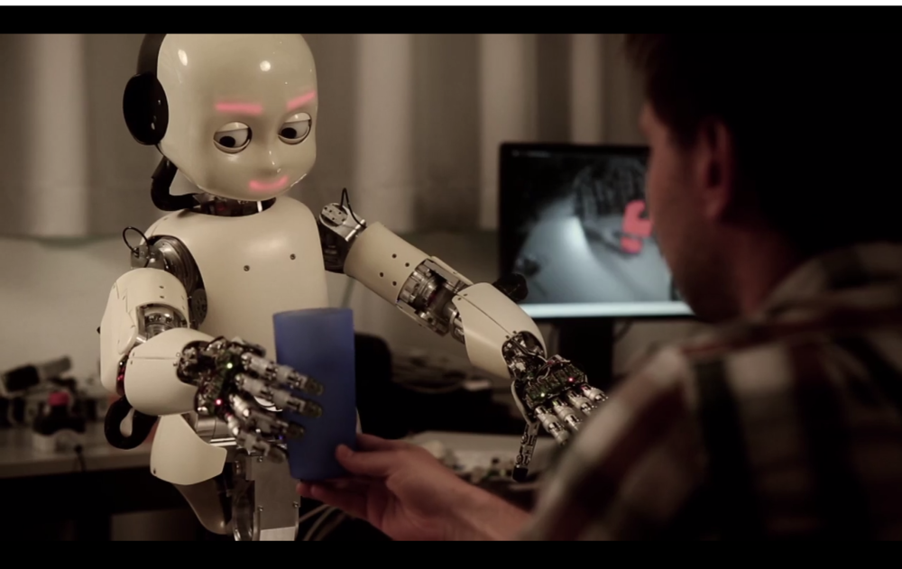 This iCub humanoid robot reaching for a cup, at IDSIA's robotics lab in Switzerland.