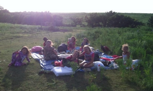 A cabin of girls enjoys an evening camping out on the prairie. Campout night is still a favorite tradition at camp wood.