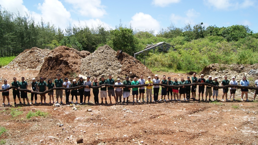 AmeirCorps University of Guam Members standing with sediment filter socks, which are mesh stockings filled with mulch that are installed in eroding hillsides to decrease erosion and promote revegetation.