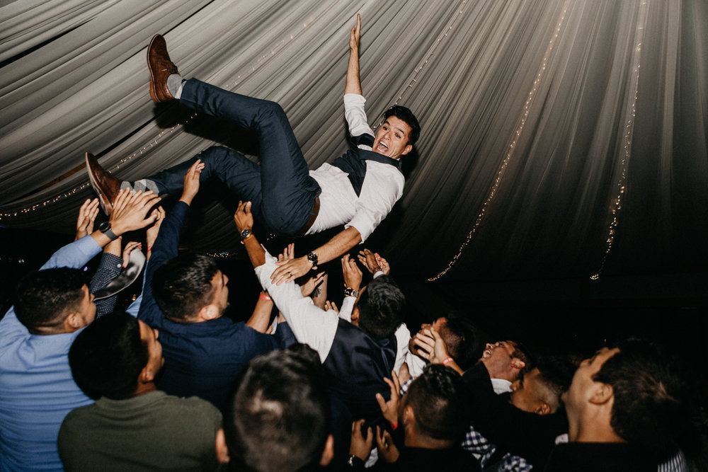 Groom photographed on his wedding day being thrown in the air
