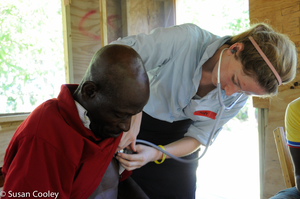 Mary examines patient in makeshift clinic, 2013.