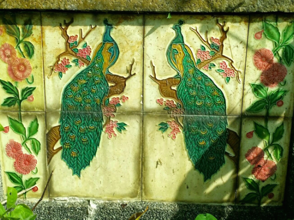 This set of peacock tiles and surrounding flowers was made in Japan.