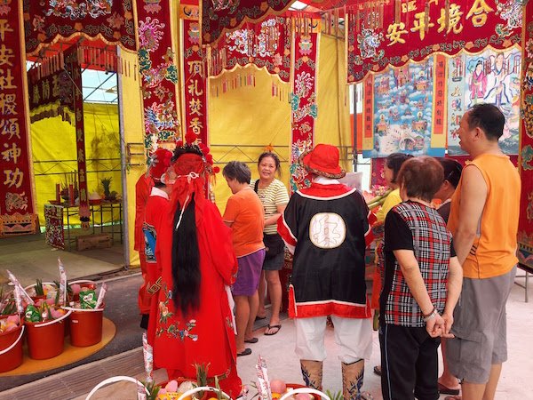 Members from the Wayang Chinese theatre group praying at the set up shrine.