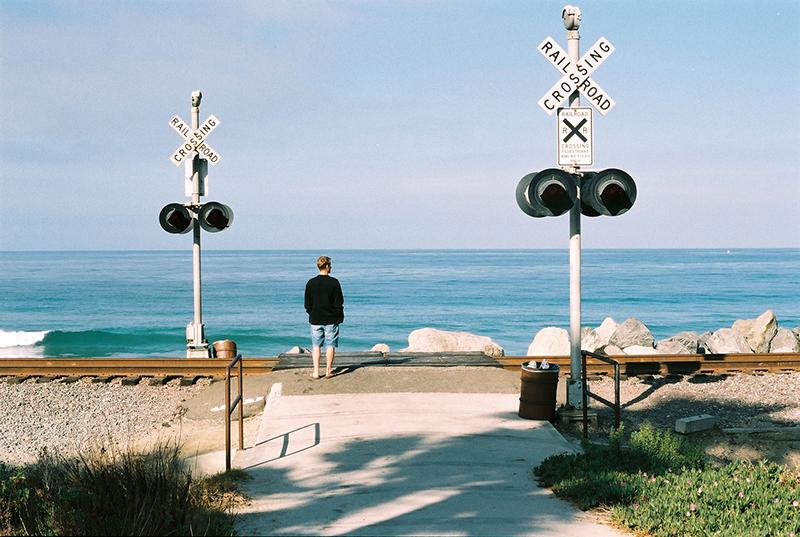 海岸に沿って走るアムトラック(長距離列車)の踏切。 散歩しながらのんびり海を眺める人もいます。