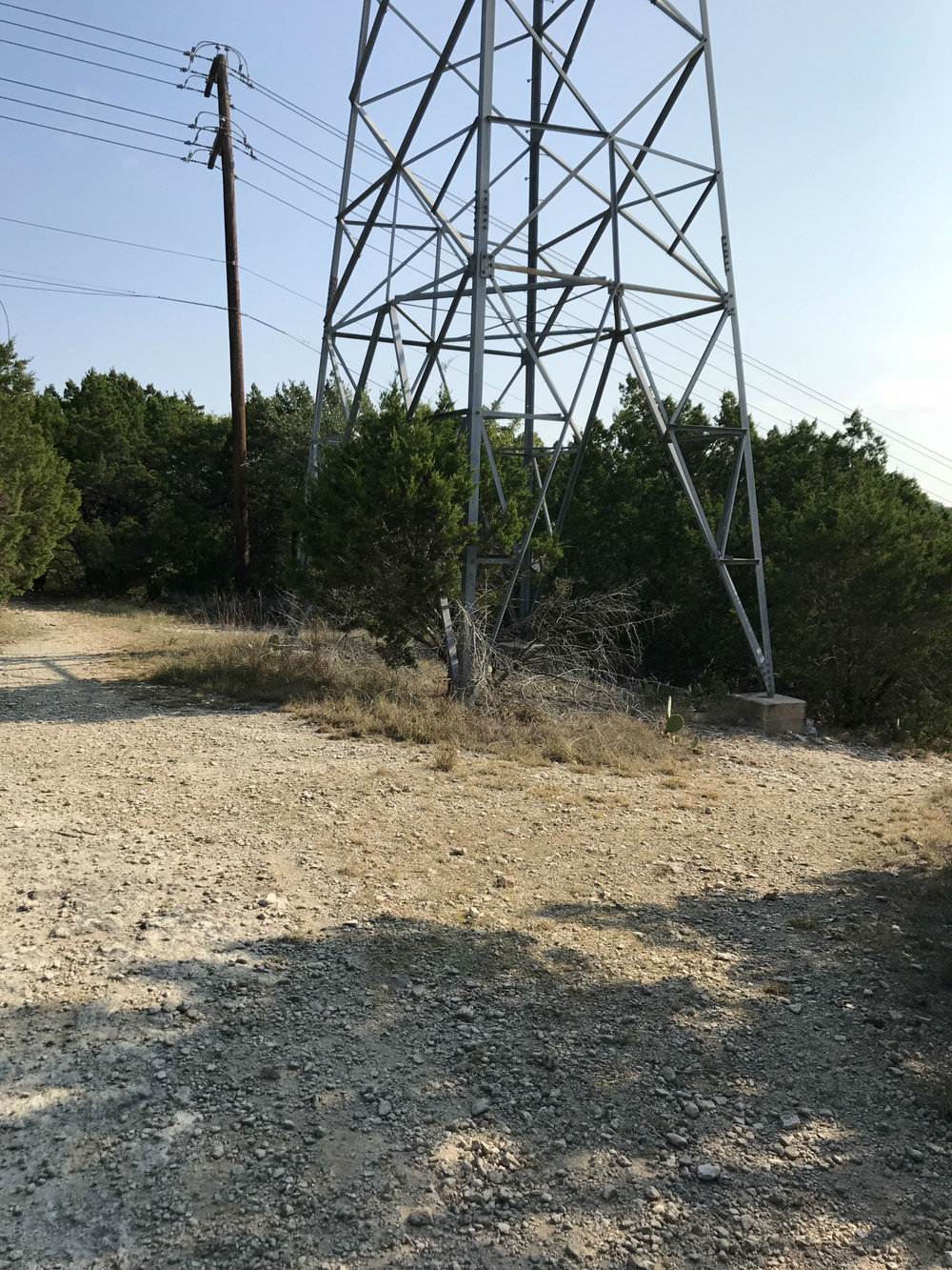 - After entering the trail branch leading to the trail head, you'll pass a power line stanchion (pictured above). The trail head is just passed the power line stanchion.At the trail head, you'll see a bench and a trail map. From the trail head, you'll head left on the blue route, following the arrows pictured in the image above.