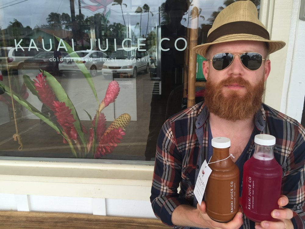 The husband at Kauai Juice Co with a 'Beetlejuice' and a pineapple/dragonfruit kombucha.