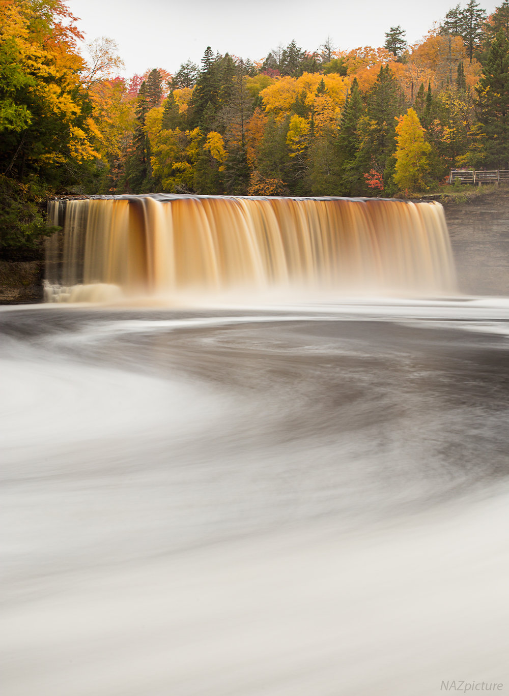 "Colors in full bloom, wrapped in a blanket of gloom at Tahquamenon Falls in Michigan's Upper Peninsula.  Its caramel-complexion is caused by tannins from cedar swamps that drain into the river, leading the site to be nicknamed ""Rootbeer Falls"""