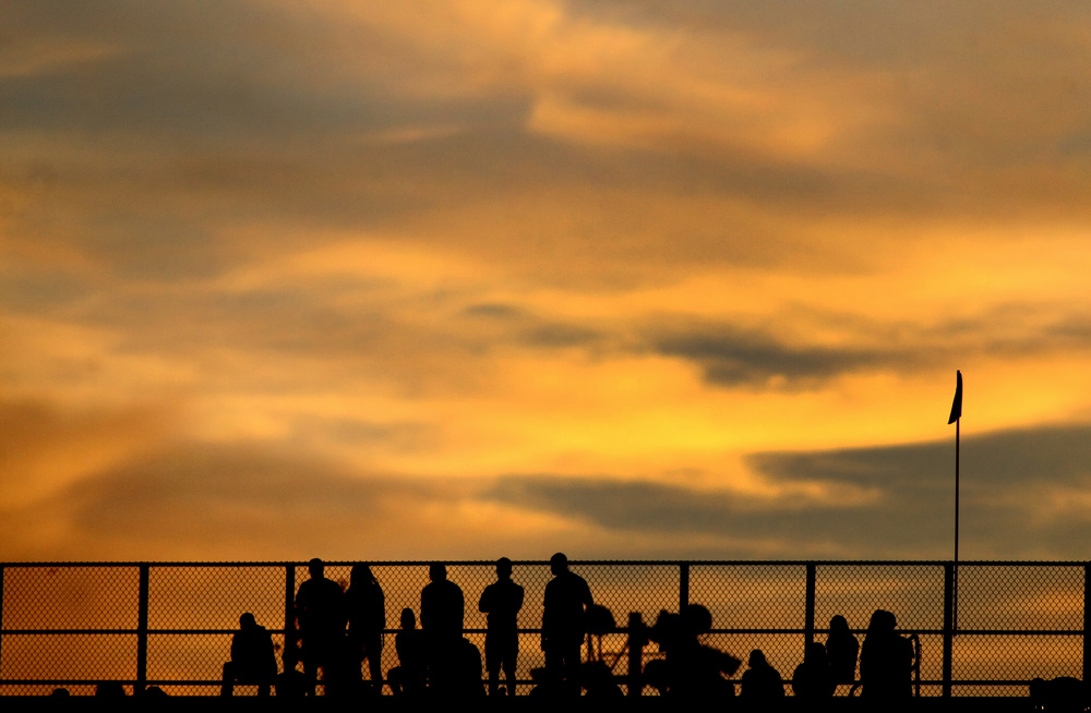 Fans watch the Norfolk State football game as the sun sets behind them during NSU's 15-14 win, Saturday, Sept. 27, 2014 at Dick Price Stadium in Norfolk.  (Jason Hirschfeld | For The Virginian-Pilot)