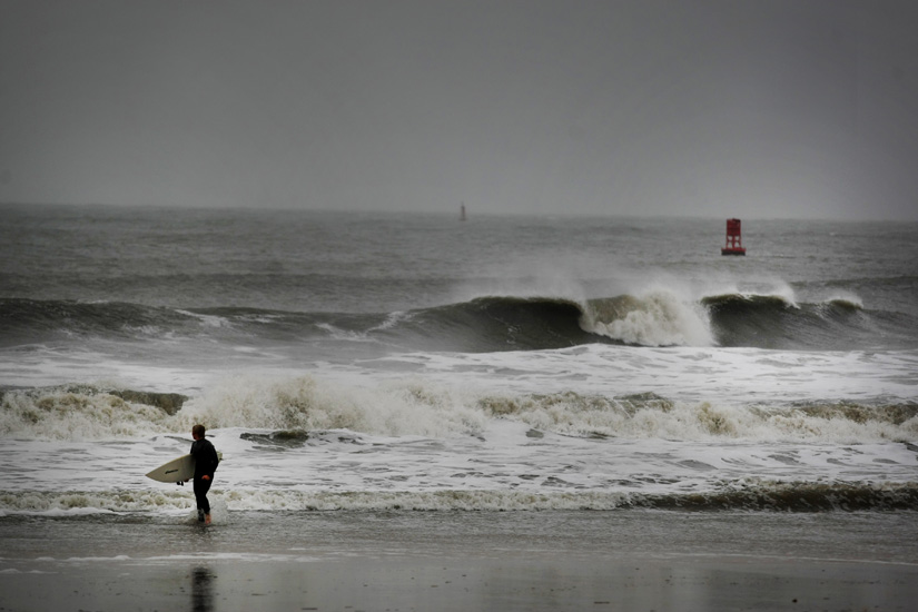 Todd Jarvis, of Virginia Beach, emerges front the surf after he determined that the currents were too hard to surf in as Hurricane Sandy pounded the Virginia coastline, Monday, Oct. 29, 2012 in Virginia Beach, Va.