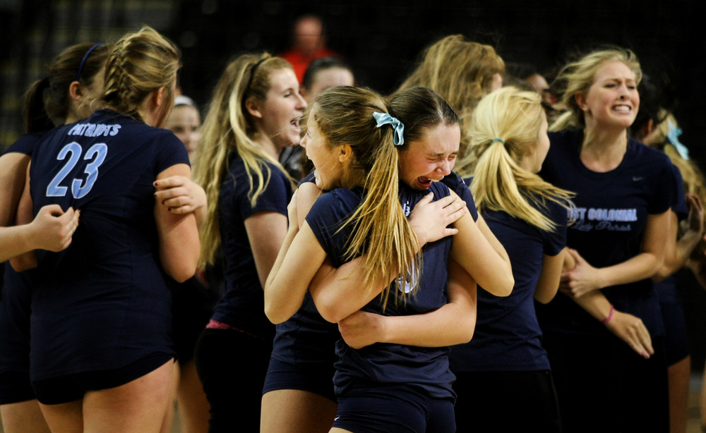 First Colonial's Rowan Ennis, center with face, and teammate Emily Guimond embrace after First Colonial beat James Madison in five-sets to claim the Group 6A girls volleyball championship, Friday, Nov. 21, 2014 at the Siegel Center in Richmond.  (Jason Hirschfeld | For The Virginian-Pilot)