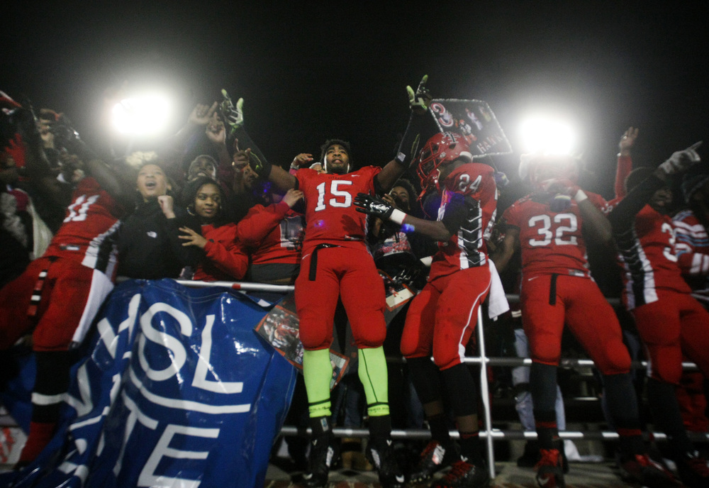 Lake Taylor's Shiheem Johnson, center, celebrates with teammates and fans after beating Salem 41-16 to win the Group 4A South championship, Saturday, Dec. 13, 2014 at Williams Field in Lynchburg. (Jason Hirschfeld | For The Virginian-Pilot)